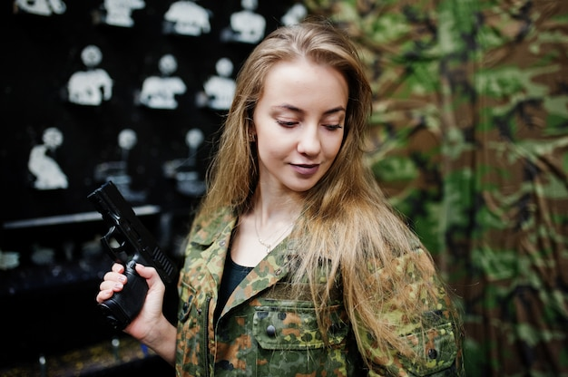 Military girl in camouflage uniform with gun at hand against army background on shooting range.