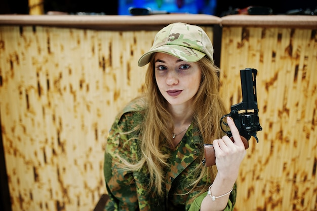 Military girl in camouflage uniform with revolver gun at hand against army background on shooting range.