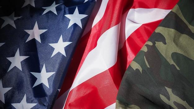 Укладка военной шляпы или сумки с американским флагом. солдатская шляпа или шлем с национальным американским флагом на черном фоне. представьте военную концепцию камуфляжным объектом и национальным флагом сша.