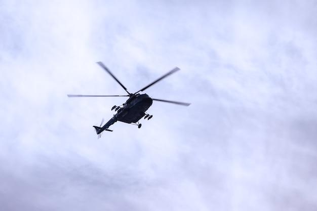 ロシア軍の軍用ヘリコプターは、テクスチャの雲で空を飛ぶ。ロシア海軍の日。海軍パレード。サンクトペテルブルク、ロシアの休日。パレードのリハーサル