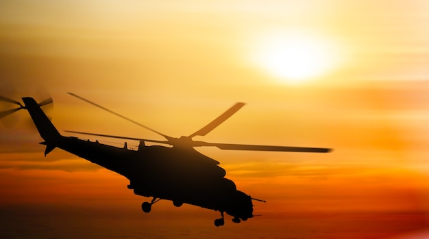 Military helicopter silhouette flying in the sky at sunset