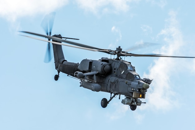 Military helicopter in the sky on a combat mission with weapons.