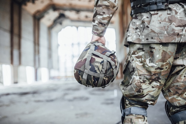 The military holds a helmet and a rifle in his hands. close-up picture.