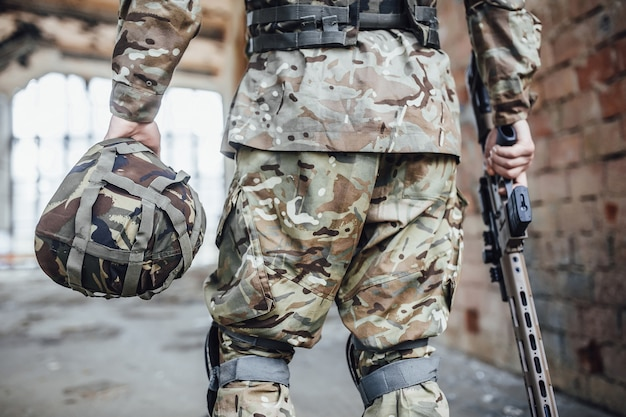The military holds a helmet and a rifle in his hands.