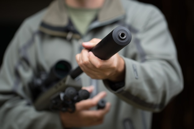 Military holds a pistol with a silencer.