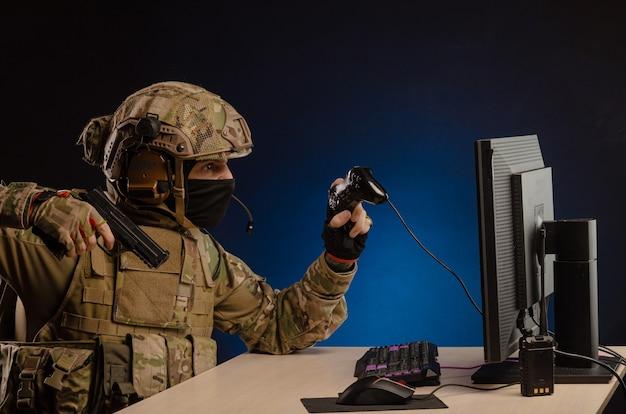 컴퓨터에 앉아 있는 제복을 입은 군대는 총으로 모니터를 겨냥한 사이버 전쟁을 이끕니다