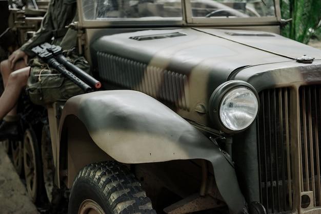 カモフラージュ面と人が機関銃で座っている軍用ジープ