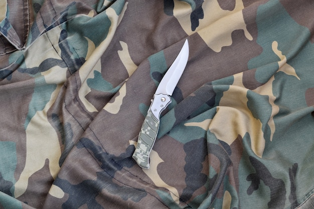 Military knife on army camouflage clothes close up. background with copy space for military or special service design