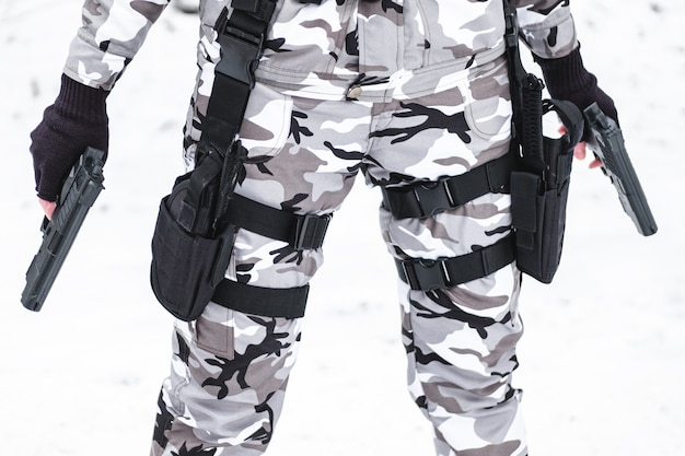 A military man in camouflage and gloves holds two pistols.