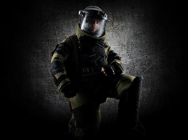 Военный в защитном саперном костюме стоит на коленях и готовится обезвредить бомбу. смешанная техника