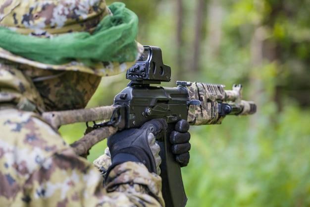 Военный в лесу с автоматом. обучение и воспитание солдат. мужчина готов стрелять
