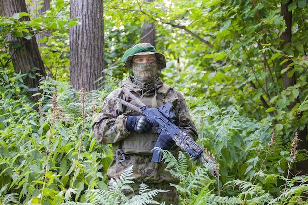 Военный в лесу с автоматом. обучение и воспитание солдат