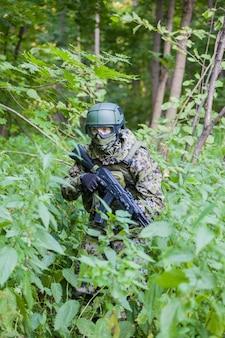 Военный в лесу с автоматом. подготовка военных к бою.
