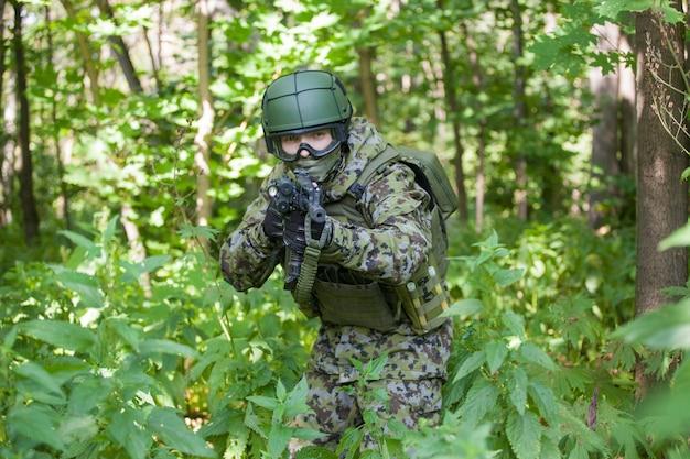 Военный в лесу с автоматом. подготовка военных к боевым действиям. пулемет прицеливается