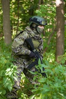 Военный в лесу с автоматом. подготовка военных к боевым действиям