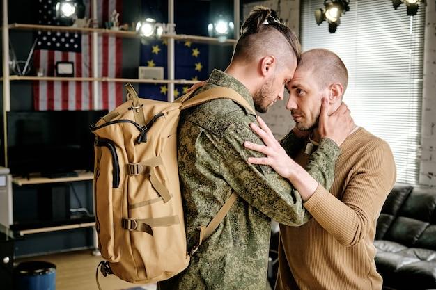 그의 남자 친구를 포옹 하 고 군사 훈련 후 돌아올 것을 약속 하는 제복을 입은 군인