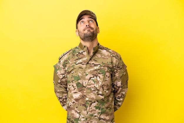 Военный мужчина изолирован на желтом фоне и смотрит вверх