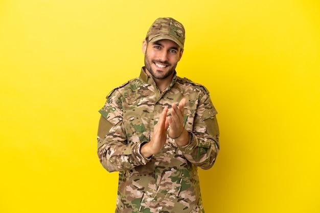 Военный мужчина изолирован на желтом фоне аплодирует после презентации на конференции