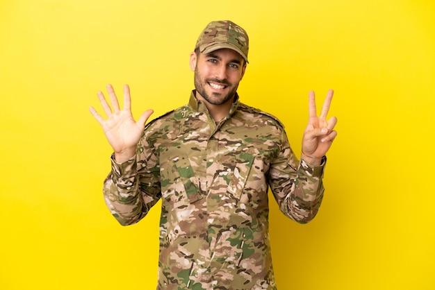 指で7を数える黄色の背景に分離された軍人