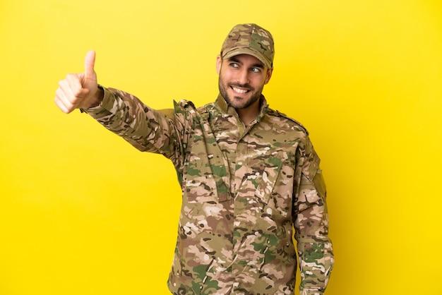 Военный мужчина изолирован на желтом фоне, показывая большой палец вверх жест