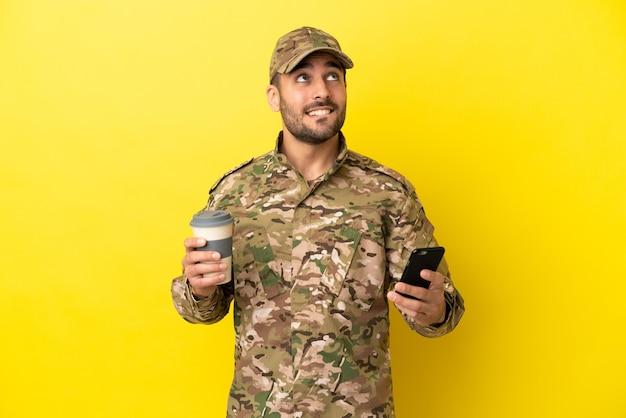 Военный мужчина изолирован на желтом фоне держит кофе на вынос и мобильный, думая о чем-то