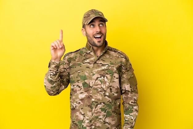 Военный человек изолирован на желтом фоне, намереваясь реализовать решение, подняв палец вверх