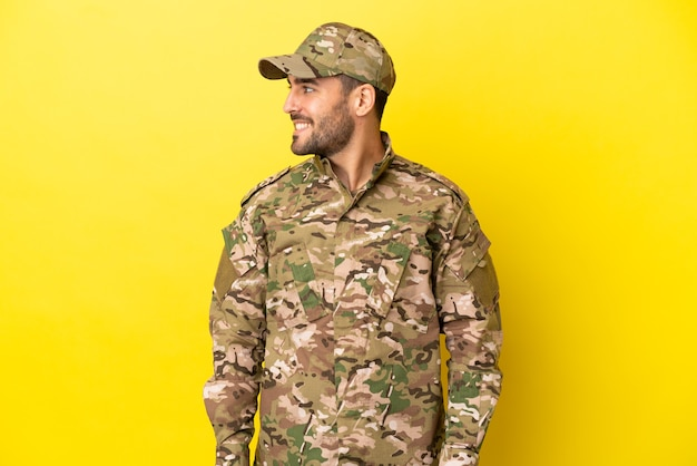 Военный мужчина изолирован на желтом фоне смотрит сторону