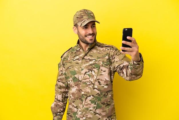 Военный человек, изолированные на желтом фоне, делая селфи