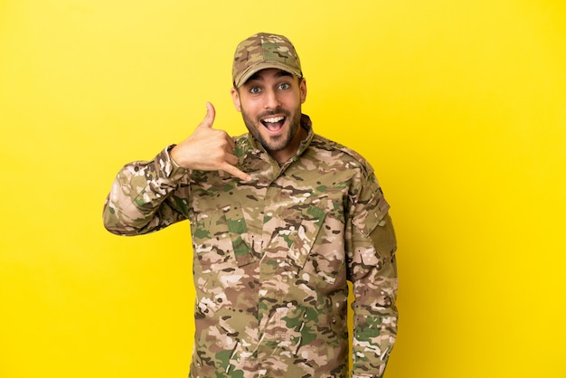 Военный человек, изолированные на желтом фоне, делая телефонный жест. перезвони мне знак