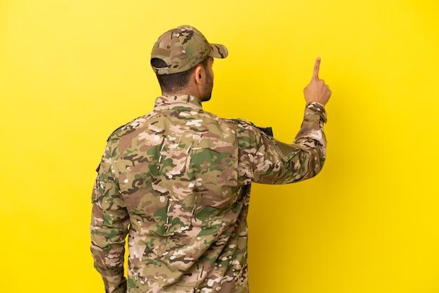 人差し指で後ろ向きの黄色の背景に分離された軍人