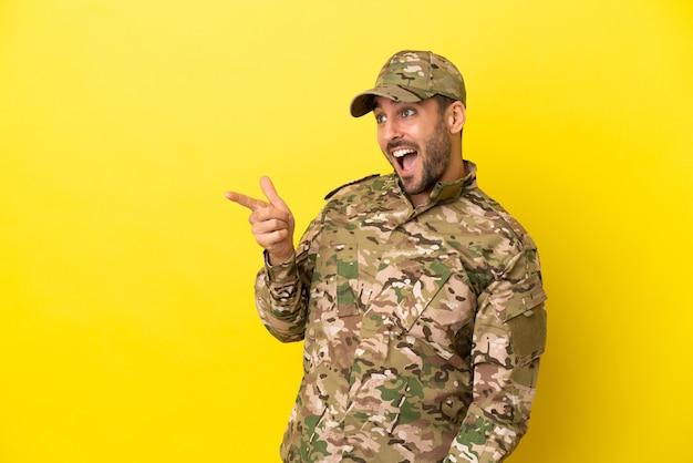 横に指を指し、製品を提示する黄色の背景に分離された軍人
