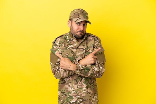Военный мужчина изолирован на желтом фоне, указывая на боковые стволы, сомневаясь