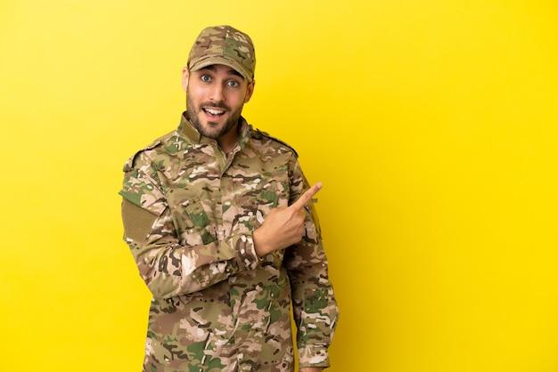 Военный мужчина изолирован на желтом фоне, указывая в сторону, чтобы представить продукт