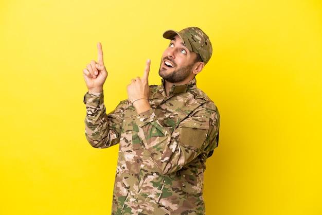 人差し指で指している黄色の背景に分離された軍人素晴らしいアイデア
