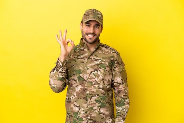 指でokサインを示す黄色の背景に分離された軍人