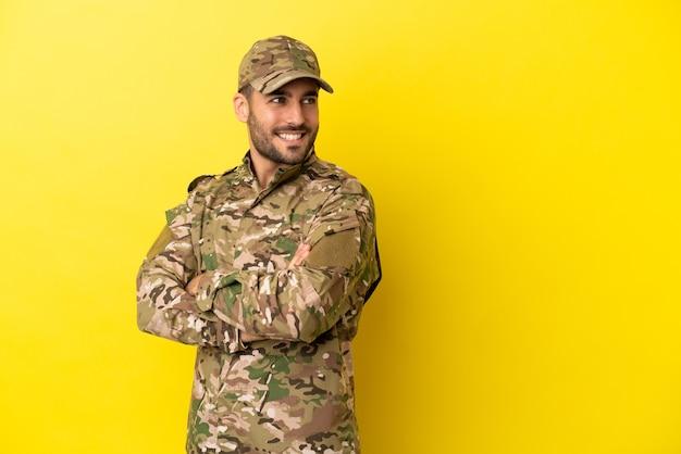 Военный человек изолирован на желтом фоне со скрещенными руками и счастлив