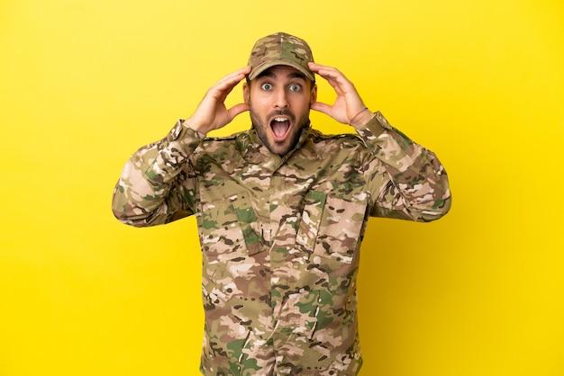驚きの表情で黄色の背景に分離された軍人