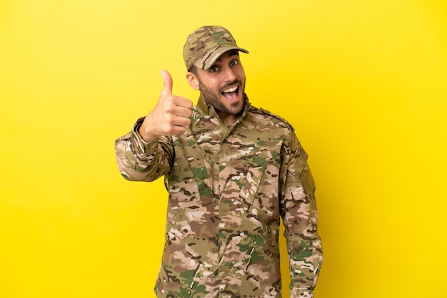 何か良いことが起こったので、親指を立てて黄色の背景に孤立した軍人