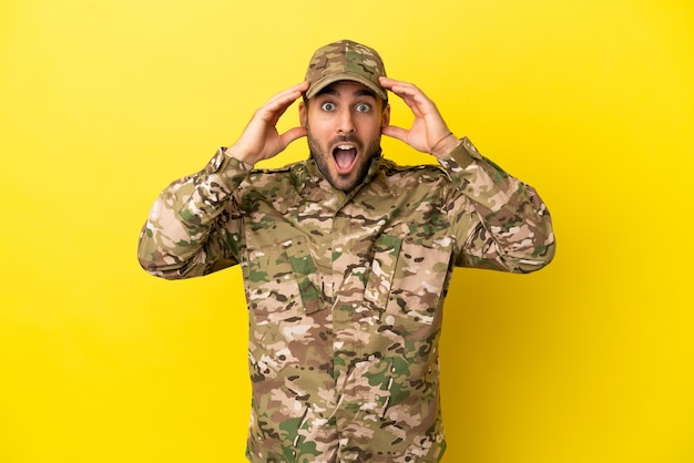 Military man isolated on yellow background with surprise expression
