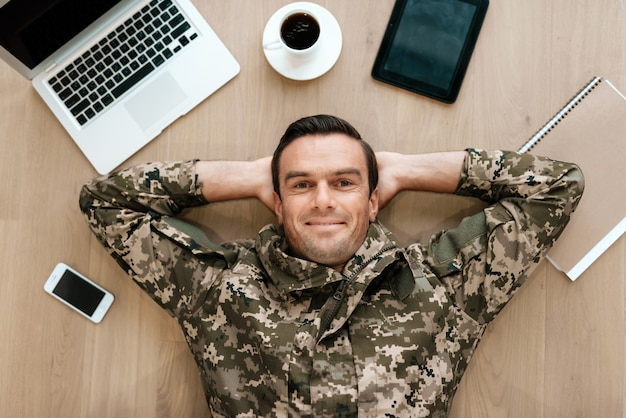 Military man lying on table with modern gadgets.