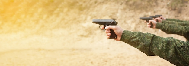 A military man in uniform holding guns