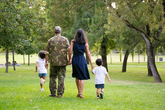 Military man walking in park with his wife and children, kids and parents holding hands. full length, back view. family reunion or military father concept