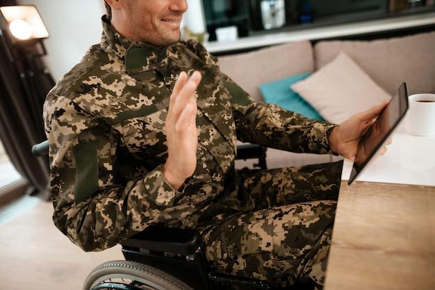 Military man in wheelchair communicates via video.