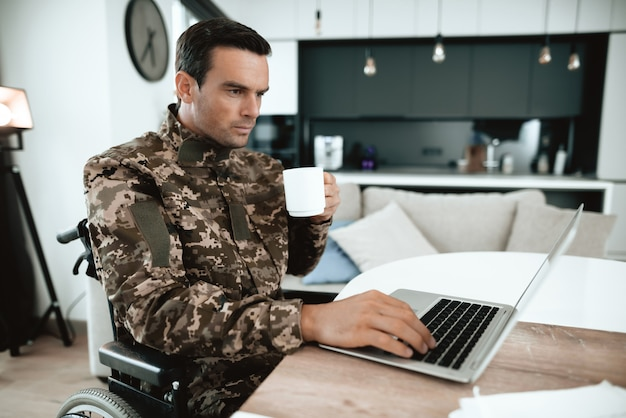 Military man in wheelchair work on laptop indoors.