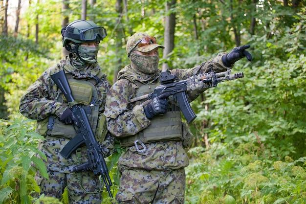 Военные в лесу с автоматом. подготовка солдат к бою