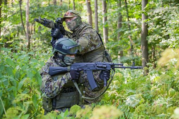 Военные в лесу с автоматом. солдаты готовы к действию