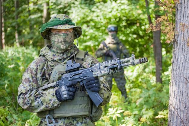 Военные в лесу с автоматами калашникова. опасность.