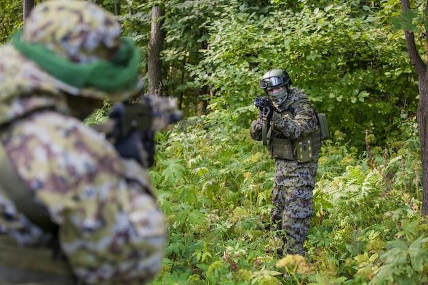 Военные в лесу с автоматами калашникова. военные действия