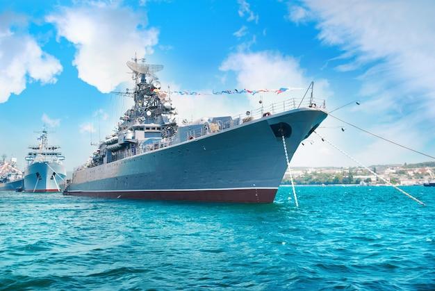 Корабль военно-морского флота в бухте. военный морской пейзаж с голубым небом и облаками