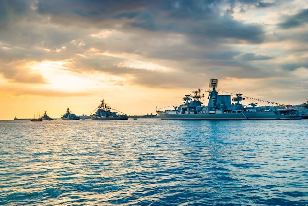 Military navy ships in a sea bay at sunset time